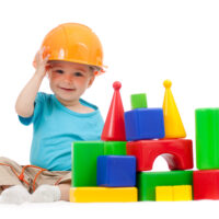 1 year old boy with hard hat and building blocks