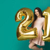 Woman holding holiday 21 birthday balloons