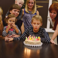 10 year old boy blowing out candles on birthday cake