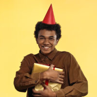 teenage boy with birthday hat on holding a gift