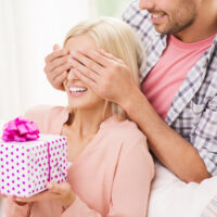 man covering eyes of young woman holding gift