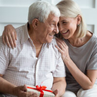 woman with older man who is holding a gift