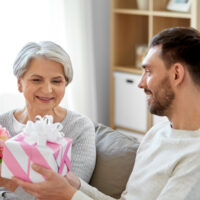 older woman receiving gift from younger man