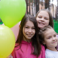 three 8 year old girls with balloons outside