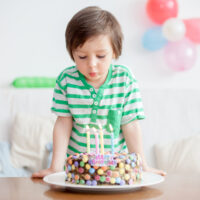 toddler boy celebrating his birthday blowing out candles